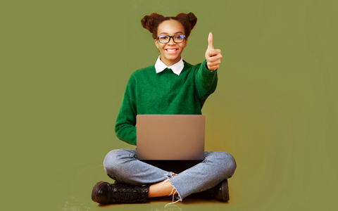 young woman sitting cross legged working on a laptop with a thumbs up
