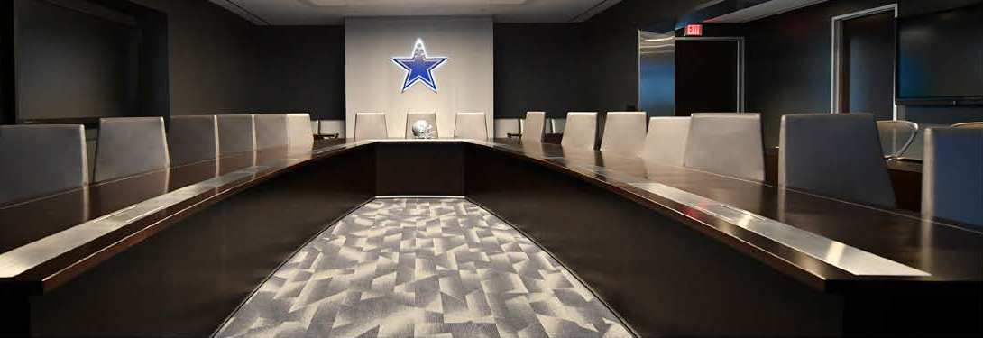 large conference room table with Dallas Cowboys star on the wall