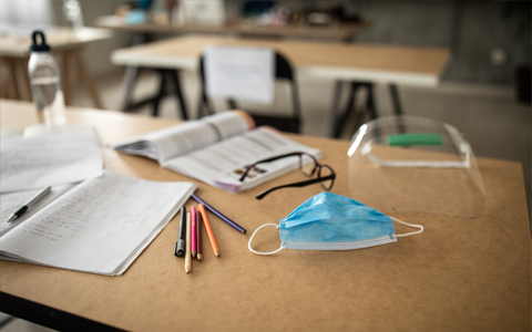 teachers desk with class materials with a surgical mask