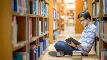 Young university student reading book in library