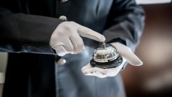 Close up of unrecognizable bell boy at a hotel ringing the bell using white gloves.