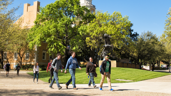 Students walking past the eagle statue on UNT campus