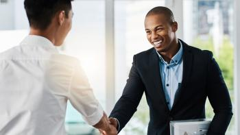 Shot of two young businessmen shaking hands in a modern office.