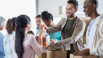 Young woman hands a bag of fruit to a young male food bank volunteer. The volunteers are receiving donations from their community to benefit a food bank.