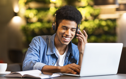 young male student wearing headphones working on a laptop